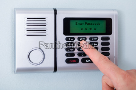 persons finger entering code in security