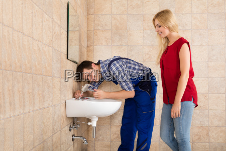 male plumber fixing tap of sink
