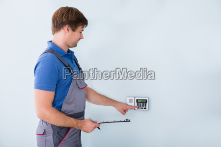 man setting security system and holding