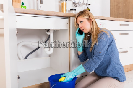 woman using mobilephone near kitchen sink