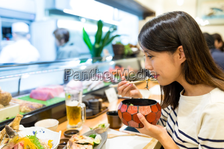 woman eating rice in japanese restaurant