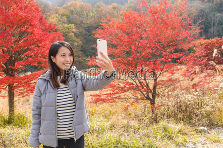 woman taking photo on cellphone with
