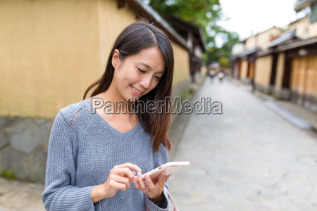 woman looking at cellphone in old