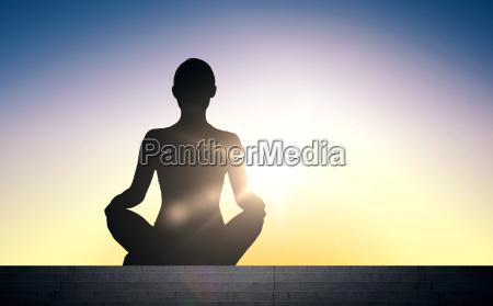 frau in yoga lotushaltung meditiert ueber
