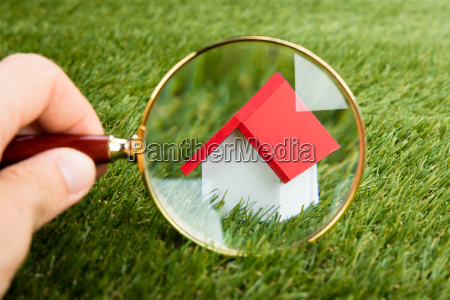 magnifying glass inspecting a model house