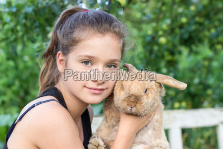 a girl holds a rabbit