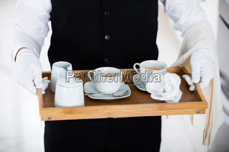 waiter carrying coffee set