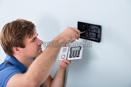 technician installing security system using screwdriver