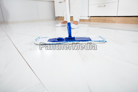 woman mopping the floor in kitchen
