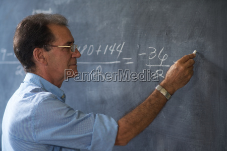 teacher writing math formulas on blackboard