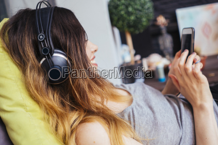 young woman wearing headphones using cell