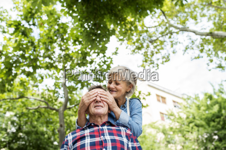 senior woman covering husbands eyes