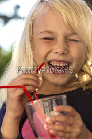 laughing little girl drinking water with