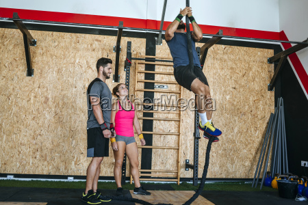 athletes climbing a rope in gym