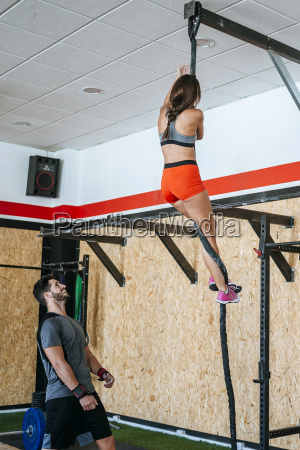 man watching woman climbing a rope