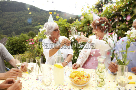 group of seniors celebrating drinking champagne