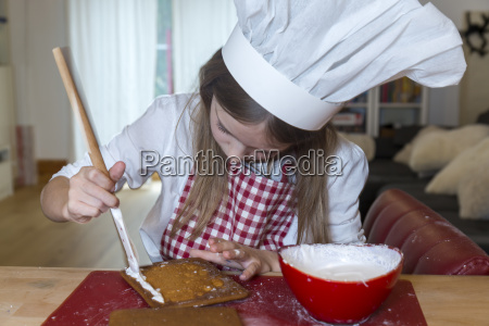 girl preparing gingerbread house