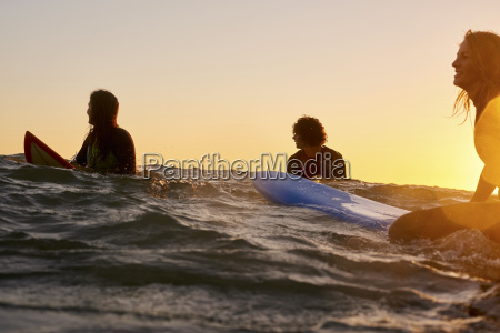 three surfers in the sea at