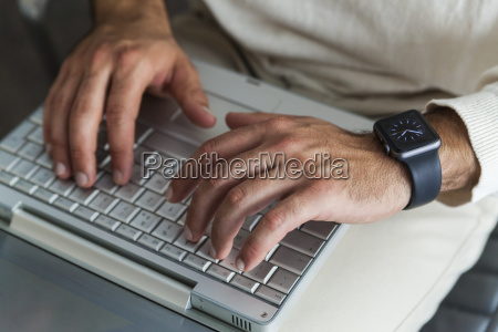 mans hands using laptop close up
