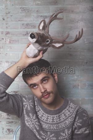 young man holding artificial deer head