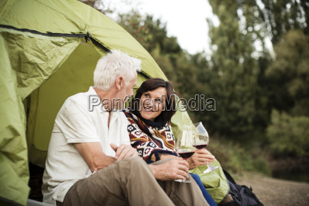 senior couple sitting with wine in