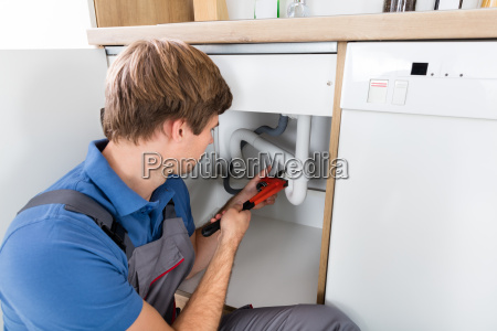 male plumber fixing sink pipe