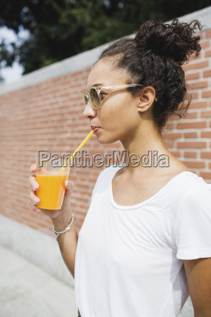 young woman drinking an orange juice