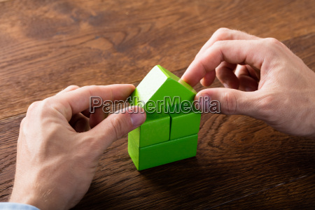 person building house of blocks
