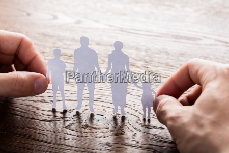 person holding paper cut of family