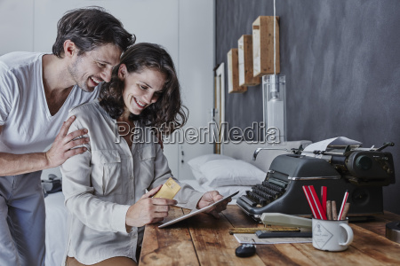 smiling couple shopping online in bedroom