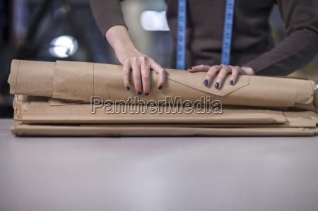 fashion designer folding up sheet samples