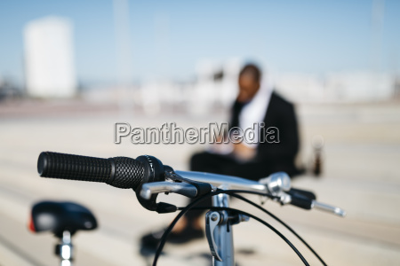 bicycle handlebar and businessman in background