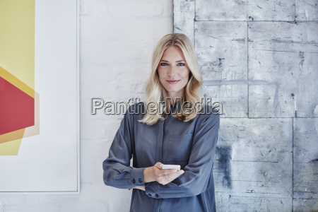 portrait of confident businesswoman with smartphone