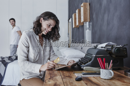 smiling woman shopping online in bedroom