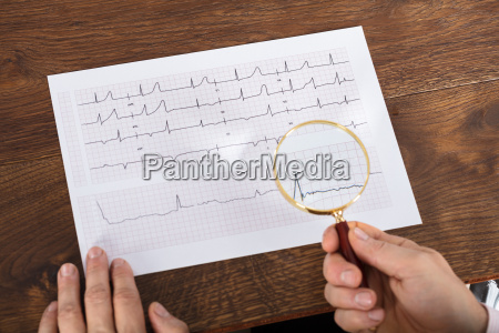 person using magnifying glass on cardiogram