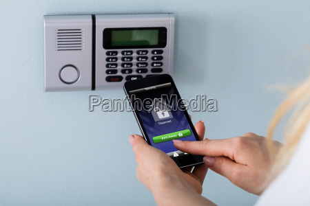 person arming the system with remote