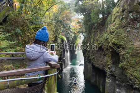 woman taking photo in takachiho gorge