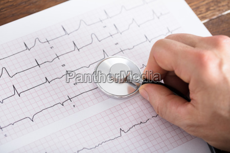 person hand using stethoscope on cardiogram