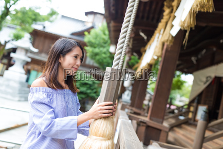 woman praying in japanese temple with