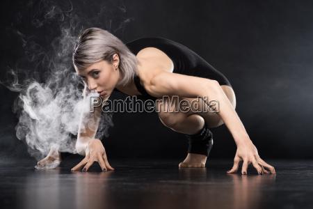 woman in bodysuit exhaling smoke on