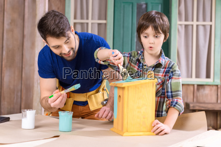 happy father and son with paintbrushes