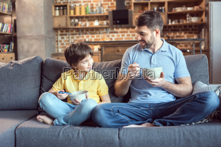 father and son sitting on couch