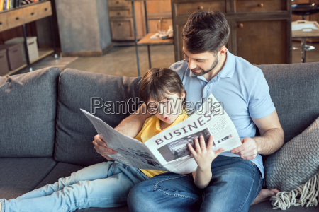 focused son reading newspaper to father