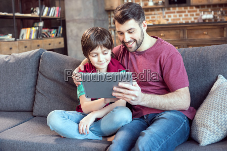 smiling father and son using digital