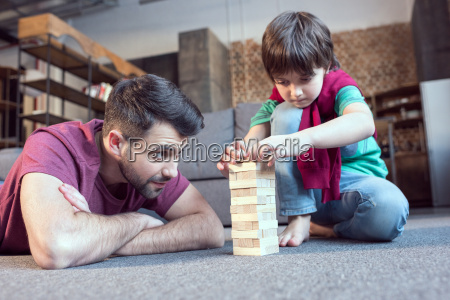 focused father and son playing jenga