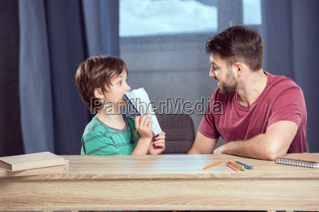 son showing done homework to father