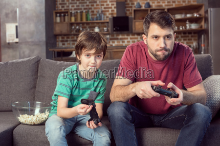focused father and son playing video
