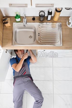 smiling plumber fixing sink