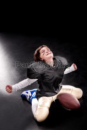 cheerful boy american football player sitting