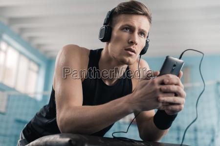 pensive young sportsman in headphones using